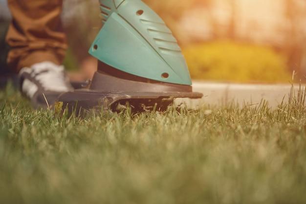 Um cara de tênis e calça está cortando grama verde com um mini cortador de grama elétrico profissional em seu ...