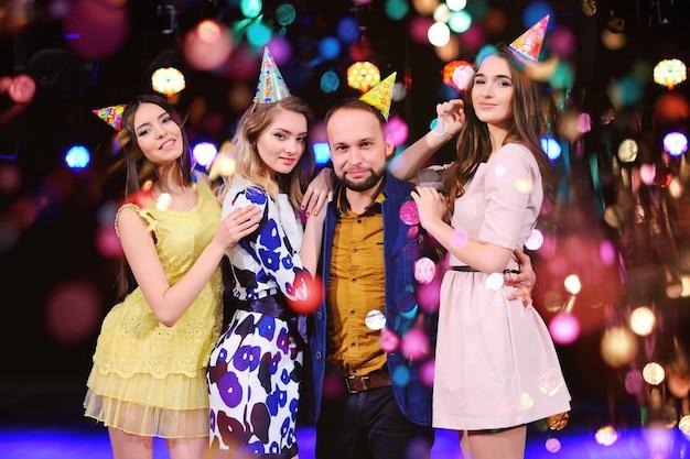 Um cara e três garotas se alegram e comemoram a festa na boate