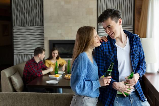 Um cara e uma garota bebem cerveja e se olham em um café.
