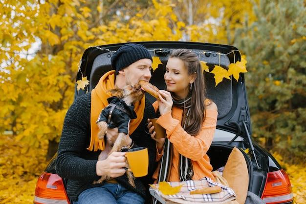 Um cara e uma garota estão sentados no porta-malas aberto de um carro com seu cachorro de estimação.