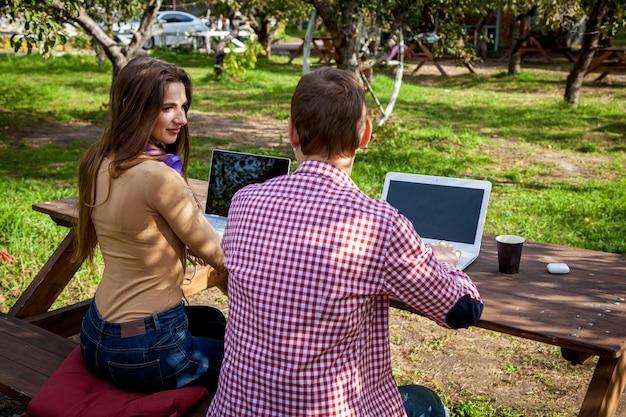 Um cara e uma garota se sentam em uma mesa de madeira no parque e trabalham em laptops com fones de ouvido. trabalho freelance ao ar livre. trabalhando fora do escritório devido à pandemia de covid 19
