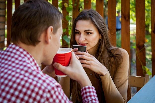 Um cara e uma garota tomam café no parque, no terraço de um café