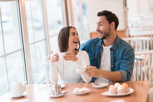 Um cara e uma menina estão sentados juntos em um café.