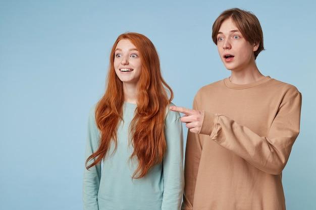Um cara e uma mulher ruiva estão parados de lado olhando a distância fascinados com a impressão