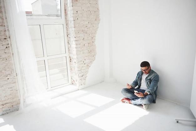 Um cara em roupas casuais está sentado em casa em um apartamento vazio, segurando um cartão de crédito
