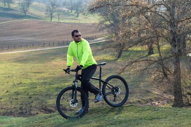 Um cara em roupas esportivas andando em uma moderna bicicleta de montanha de carbono com um garfo de suspensão a ar