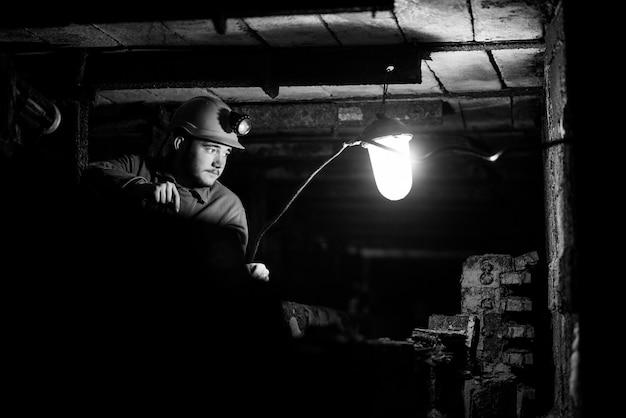 Um cara em um traje de proteção e capacete senta-se em um túnel com uma página de recados queima