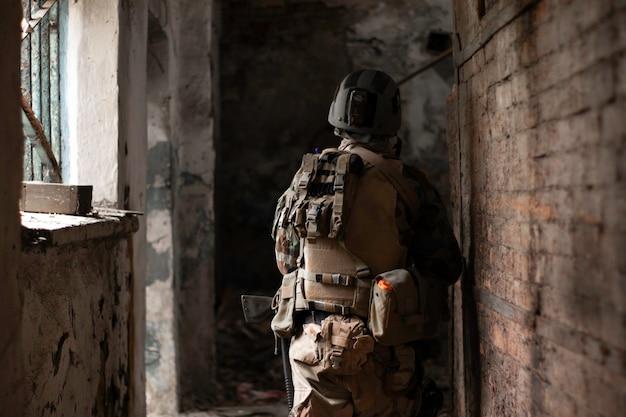 Um cara em um uniforme militar americano em um antigo corredor abandonado move-se com uma arma de airsoft sports game