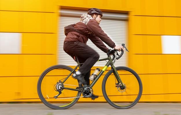 Um cara em uma bicicleta de cascalho passa por uma parede amarela