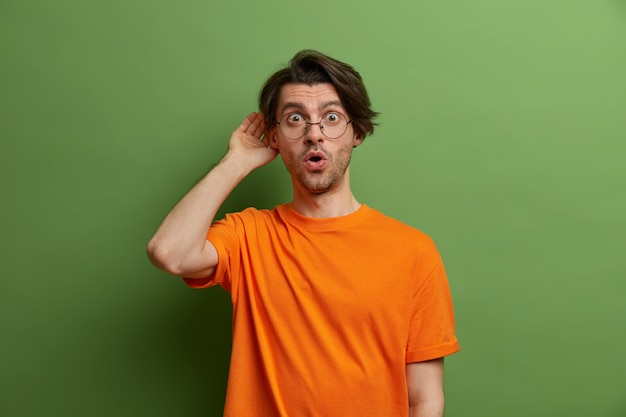 Um cara emocional atordoado escuta informações, mantém a mão perto do ouvido, chocado ao ouvir algo inesperado, surpreso com fofocas, usa óculos e camiseta laranja, fica encostado na parede verde