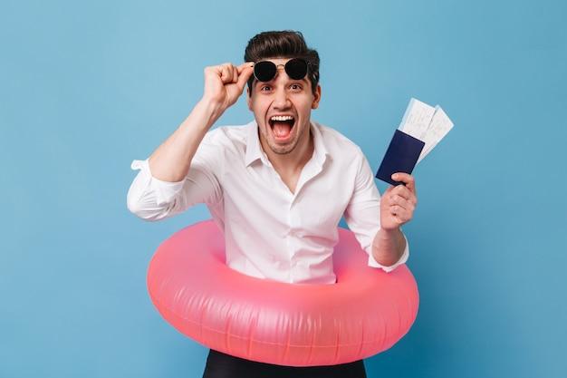 Um cara emocional de olhos castanhos tira os óculos escuros e acena alegremente o passaporte e as passagens. homem de camisa branca, posando com anel de borracha contra o espaço azul.