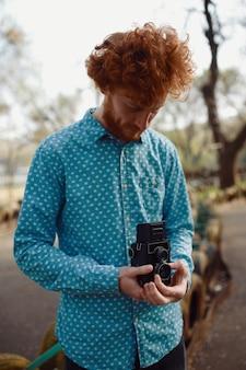Um cara encaracolado avermelhado com uma câmera de filme de médio formato nas mãos, tirando fotos
