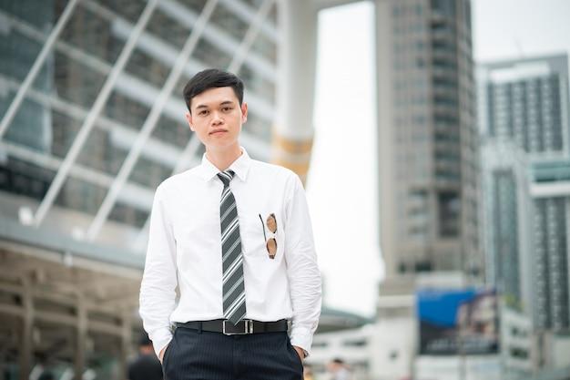 Um cara esperto está parado na cidade, ele está vestindo camisa branca e gravata.