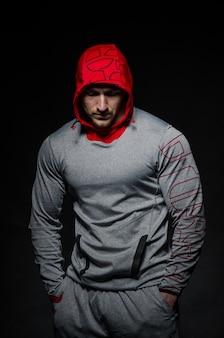 Um cara esportivo fica contra um fundo escuro em uma capa. esportes, beleza