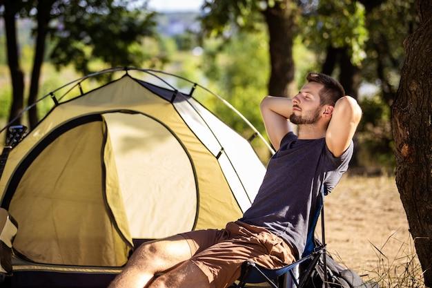 Um cara está descansando perto de uma barraca em uma cadeira dobrável na floresta.