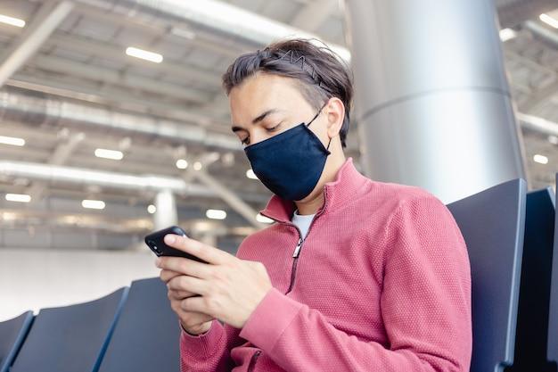 Um cara está esperando por um voo com uma máscara médica no rosto no saguão do aeroporto.