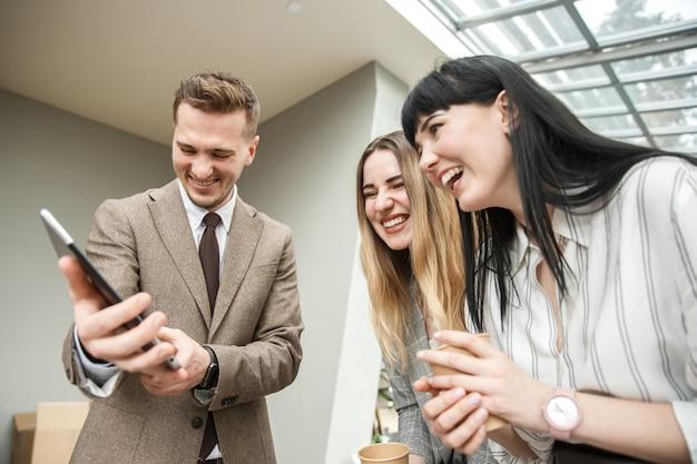 Um cara está mostrando algo em seu tablet para duas meninas. eles estão rindo juntos.