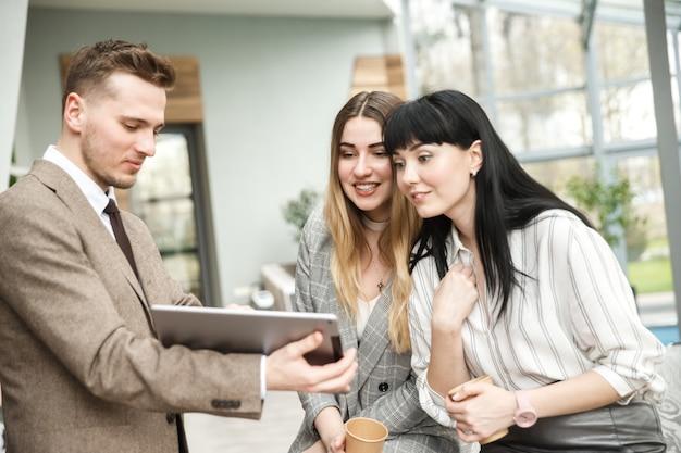 Um cara está mostrando algo em seu tablet para duas meninas