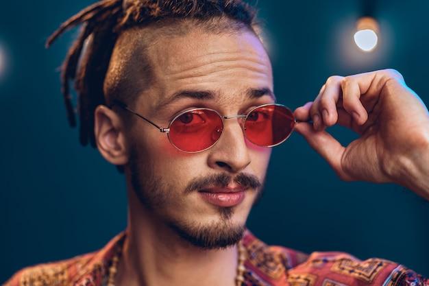 Um cara estiloso com dreads e óculos de sol rosa close-up