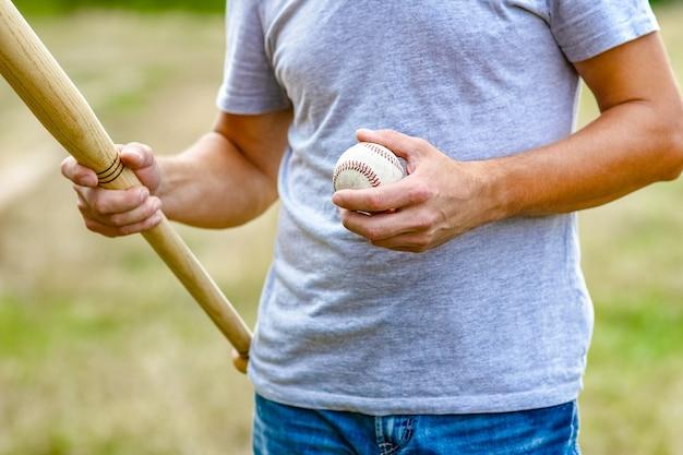 Um cara feliz com taco de beisebol no conceito de natureza no parque