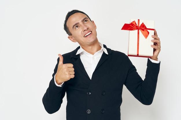 Um cara feliz com uma caixa de presente mostra um polegar