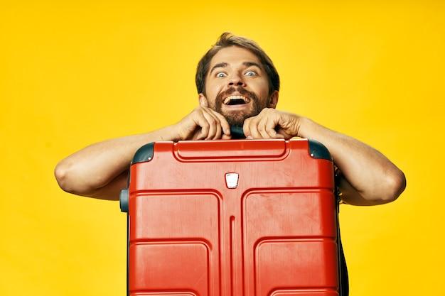 Um cara feliz com uma mala vermelha em uma risada amarela