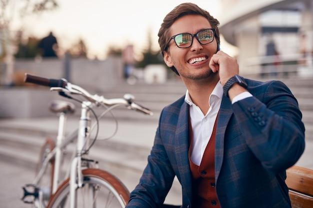 Um cara feliz e formal com uma bicicleta conversando no telefone na cidade