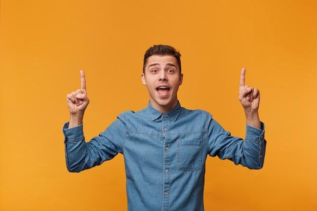 Um cara feliz e inspirado mostra o dedo indicador no espaço vazio acima de sua cabeça