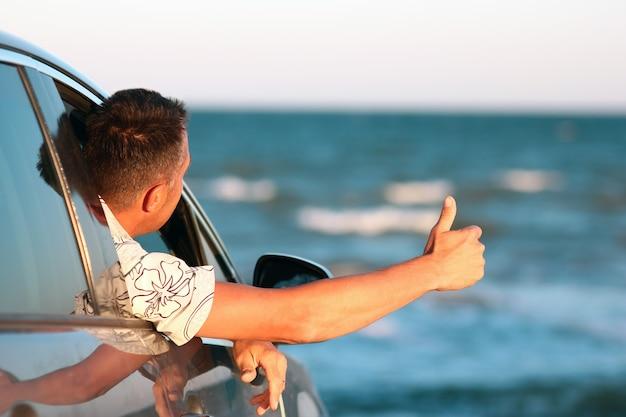 Um cara feliz no carro à beira-mar na natureza em viagem de férias