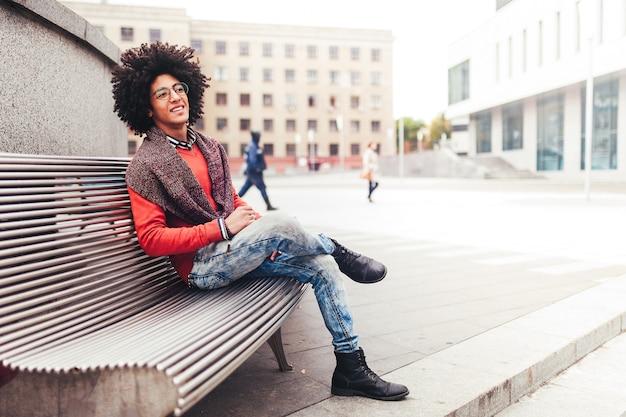 Um cara jovem e bonito egípcio encaracolado sentado num banco