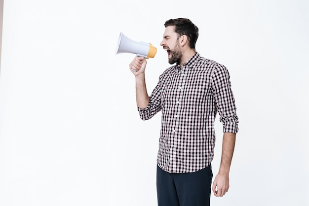 Um cara jovem grita em um megafone de dor.