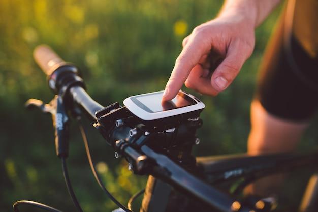 Um cara jovem morena em uma bicicleta de montanha usa um computador de ciclismo, um navegador no pôr do sol de campo do dia