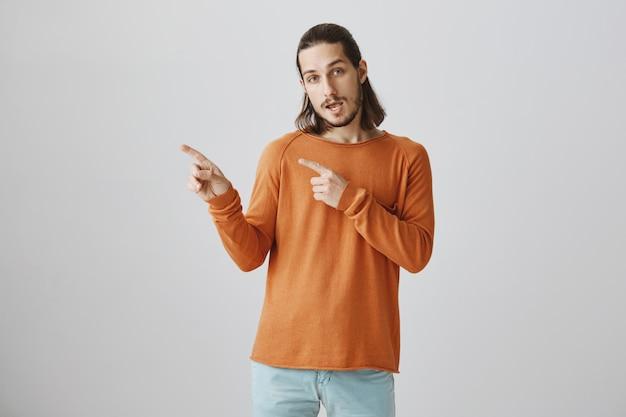 Um cara legal bonito e moderno apontando o dedo para a esquerda, convidando para dar uma olhada