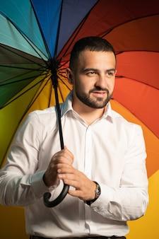 Um cara legal com uma barba estilosa e camisa branca está com um guarda-chuva de arco-íris nas costas. cara bonito em apoio à sociedade lgbt.