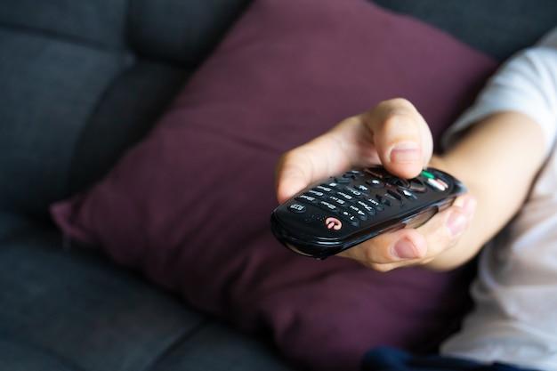 Um cara magro em roupas domésticas se senta em um sofá e assiste tv. cara entediada com controle remoto de tv