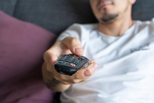Um cara magro em roupas domésticas se senta em um sofá e assiste tv.
