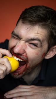 Um cara morde um limão em um fundo vermelho. retrato de close-up
