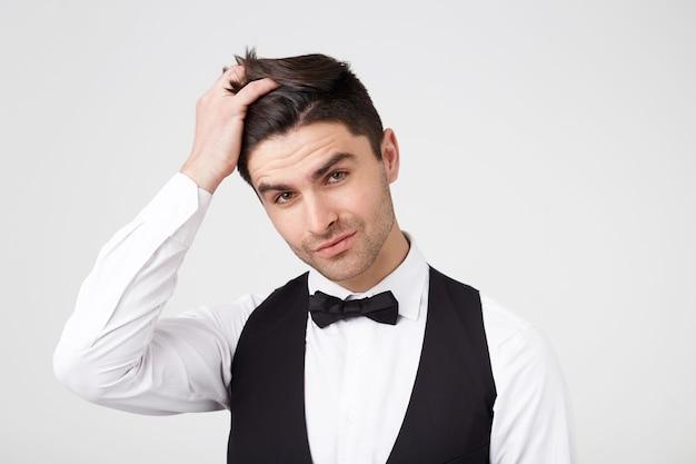 Um cara moreno atraente com cerdas claras, bem vestido alisa o cabelo de maneira divertida,