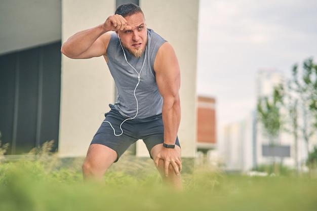 Um cara musculoso com uma longa barba enxuga o suor da testa com o punho enquanto está de pé na rua