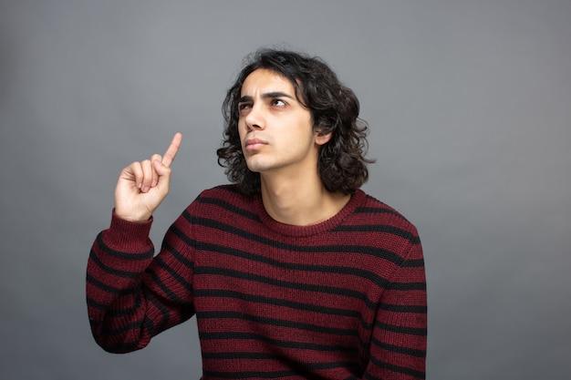 Um cara pensando enquanto o dedo para cima