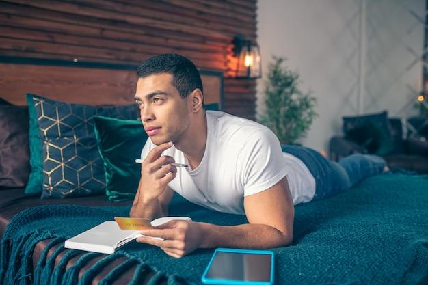 Um cara pensativo com um cartão de crédito na mão, deitado na cama, olhando para frente.