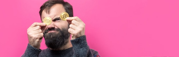 Um cara pensativo com uma barba contra um fundo rosa pensando na pergunta, expressão pensativa