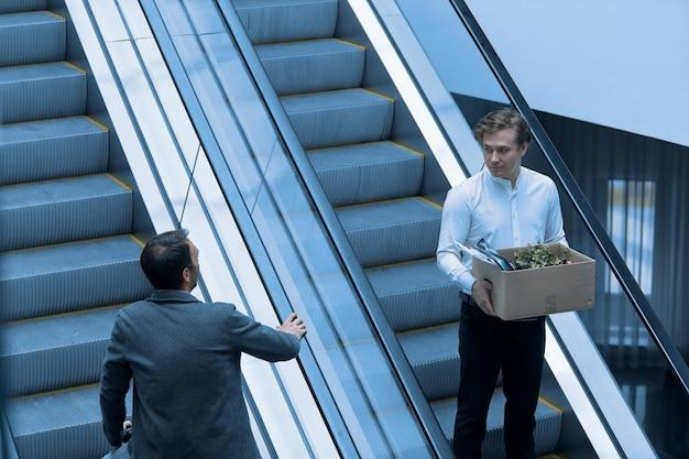 Um cara que é demitido do trabalho desce a escada rolante com uma caixa de coisas passando por seu chefe.