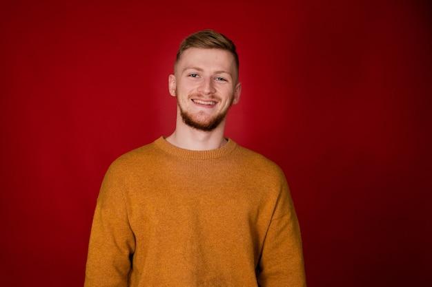 Um cara ruivo sorridente com um suéter mostarda olhando para a frente