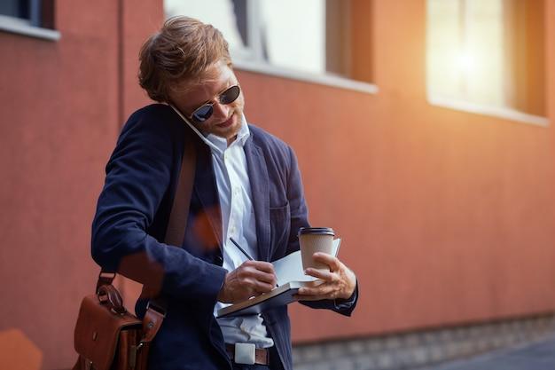 Um cara sério e atraente de terno fala ao telefone com um cliente em movimento