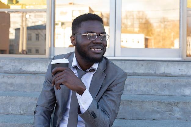 Um cara sorridente afro-americano escreve sms para amigos no telefone.
