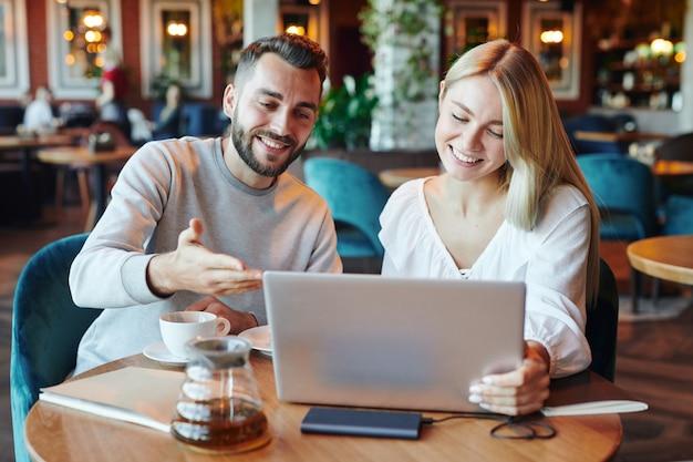 Um cara sorridente fazendo uma apresentação para sua linda namorada ou colega de grupo enquanto os dois estão sentados em frente ao laptop no café da faculdade