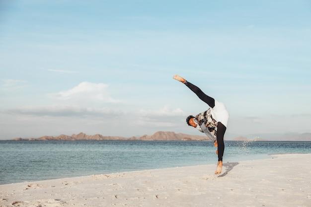 Um cara treinando arte marcial de chute de taekwondo na praia