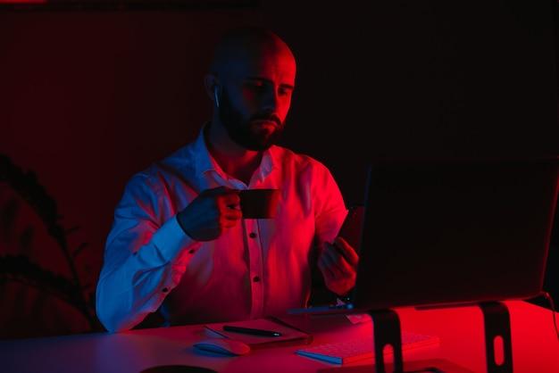 Um careca com barba trabalhando remotamente em um laptop em casa