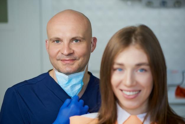 Um careca sorrindo dentista de meia-idade, juntamente com seu jovem paciente do sexo feminino no consultório do dentista